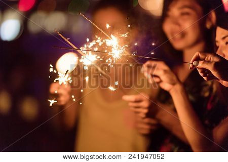 Blurred Of Sparklers With Group Of Friends Having Fun For Celebration And Hand Holding A Burn Sparkl