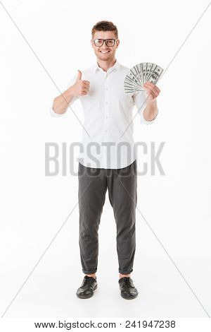 Full length portrait of a confident young man in eyeglasses holding money banknotes and showing thumbs up isolated over white background