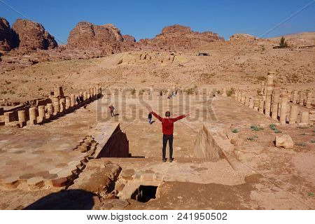 Roman Columns With A Young Man Standing In The Great Temple Complex In Petra (rose City), Jordan.