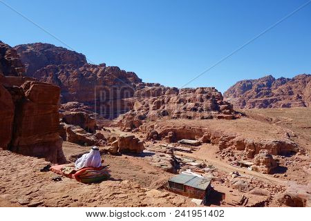 Panoramic View Of Petra With A Lying Bedouin Wearing The Traditional Clothes, Unesco World Heritage