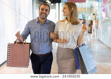 Smiling Male And Female Consumers Walking Between Shops In Mall. Joyful Couple Visiting Shopping Mal