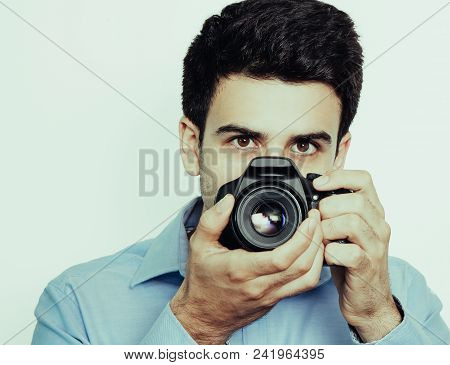 Portrait Of Male Photographer Working And Using Camera. Concentrated Man Peeping Out From Behind Pho