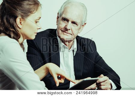 Serious Businessman Looking At Business Consultant. Confident Female Financial Advisor Giving Advice