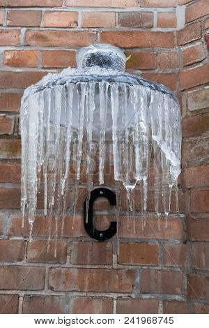 Lamppost On Building Covered With Icicles In Winter