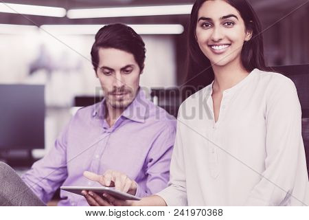 Young Latin-american Businesswoman Holding Digital Tablet, Looking At Camera And Smiling. Her Seriou