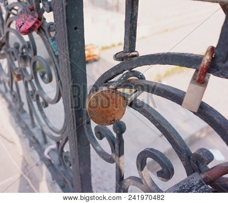 Old Padlock On A Decorative Metal Fence. Russian Wedding Tradition To Attach The Padlock As A Symbol