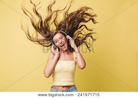 Image of amusing woman 20s singing and having fun with shaking hair while listening to music via headphones isolated over yellow background