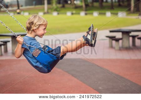 Funny Kid Boy Having Fun With Chain Swing On Outdoor Playground. Child Swinging On Warm Day. Active