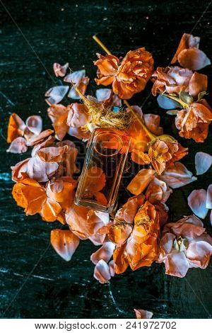 Medicinal and floral essence of Rose or gulab popularly known as gulab jal or gulab ka pani in Asia with fresh bright rose petals on wooden surface. poster