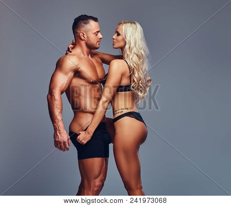 Handsome Muscular Shirtless Male And Attractive Fitness Blond Female Posing Over Grey Background.