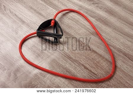 Red Elastic Expander In The Form Of Heart On Wooden Background