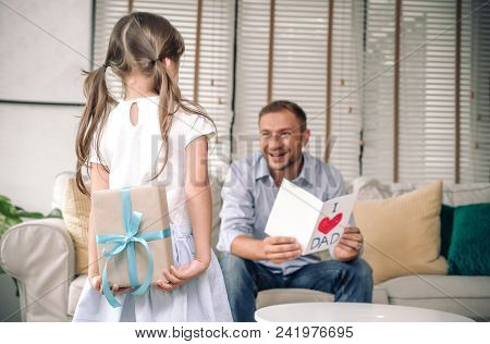 Cute Little Girl Is Giving Card Her Handsome Father And Surprising  A Gift Box At Home In The Living