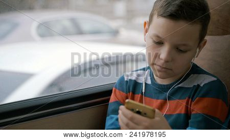 Close-up Shot Of A Young Boy Traveling By Bus Through City. He Using Social Network On His Smartphon