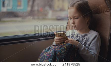 Young, Beautiful Girl Passenger With School Bag In The Moving School Bus Using Social Network On Her