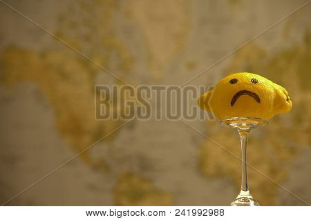 Concept: When Life Gives You Lemons. Big Lemon With A Sad Face On In Focus. World Map Out Of Focus I