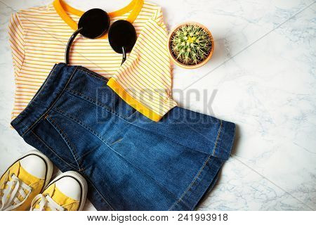 Outfit Of Teen Or Woman Clothes And Accessories On Marble Background. Denim Skirt, T-shirt With Yell