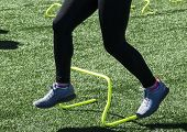 A high school track and field athlete is running over yellow mini banana hurdles during strenght and speed practice. poster