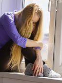 People and solitude concept. Alone sad young woman long hair teen girl sitting on window sill lost in thought poster