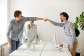 Cheerful male colleagues fist bumping celebrating successful teamwork in office, friendly happy motivated coworkers excited by good work result congratulating each other with professional achievement poster