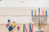 Hanukkah/ Chanukah Jewish holiday background with menorah (Judaism candelabra)  burned candles and traditional Dreidrel game toy on wood table backdrop poster