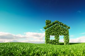 Eco Friendly Living Concept. 3d Rendering Of Green House Icon On Fresh Spring Meadow With Blue Sky I