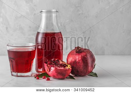 Pomegranate Juice In A Bottle With Glass Of Juice And Fresh Pomegranate Fruits On Marble Table. Heal