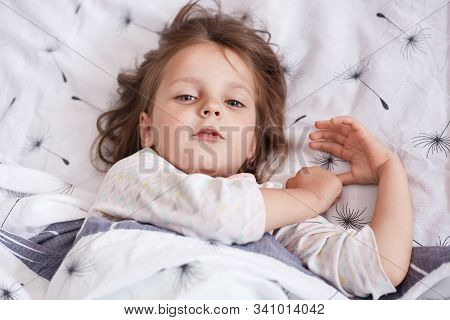 Top View Of Little Sleepy Child Looking Directly At Camera, Waking Up Early, Lying In Bed, Having Fa