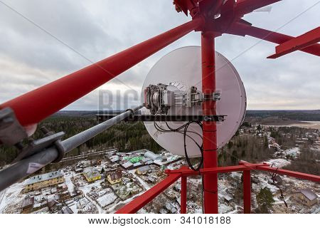 Red Telecommunication Tower Or Mast With Microwave, Radio Panel Antennas, Outdoor Remote Radio Units
