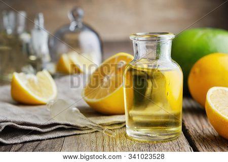 Bottle Of Citrus Lemon Essential Oil And Citrus Fruits On Table.