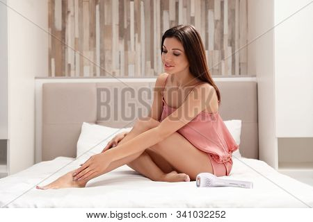 Young Woman Touching Soft Skin After Epilation In Bedroom