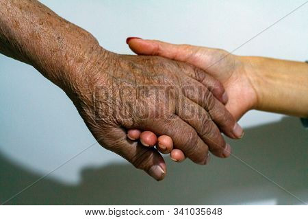 An Elderly Woman Grandmother And A Young Girl Hold Hands. Support For The Elderly From Young People