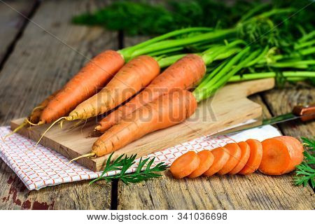 Fresh Carrots And Sliced Carrot On A Wooden Blackboard With Knife, Dish Cloth And Cutting Board. Sel