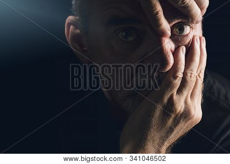 Portrait Of A Man Who Emphasizes An Eye With His Hands