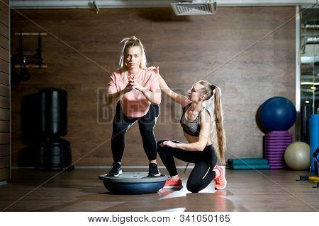 Female Trainer Controls Balancing Technique With Bosu