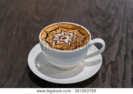 Cup Of Beautiful Hot Mocha Art Latte Coffee On Table