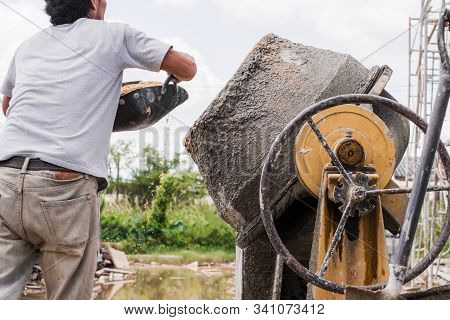 Construction Worker Load Sand Into Cement Mixer Using Black Scoop. Cement Mixing Operation.