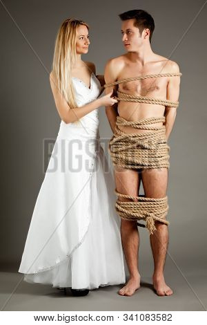 Young Beautiful Blond Woman In Wedding Dress Standing Near Her Naked Man Tied Up With Ropes Over Gre