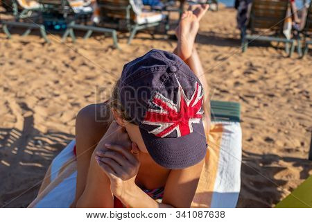 The Girl Sunbathes On The Beach In A Baseball Cap With The Image Of The British Flag. British State