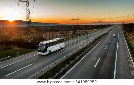 White Bus Traveling On A Country Highway Under Amazing Orange Sunset Sky. Highway Transportation Of