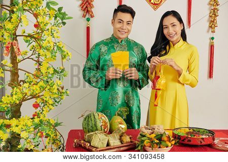Cheerful Young Asian Couple In Room Decorated For Tet Celebration Standing At Table Served With Trad