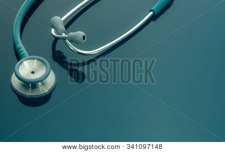 Closeup Green Stethoscope On Doctor Table Or Nurse Desk. Health Checkup Or Health Insurance Concept.