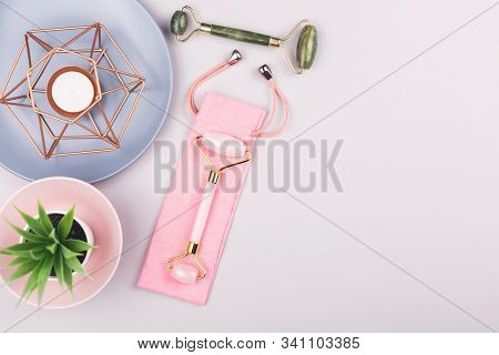 Beauty Composition With Trendy Pink And Green Jade Rollers On Blue Background. Selfcare, Home Spa An