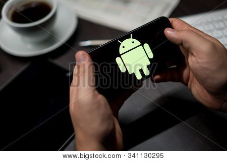 New York, New York / USA - 11 11 2019: Logo of Android on the iPhone X in hands in office