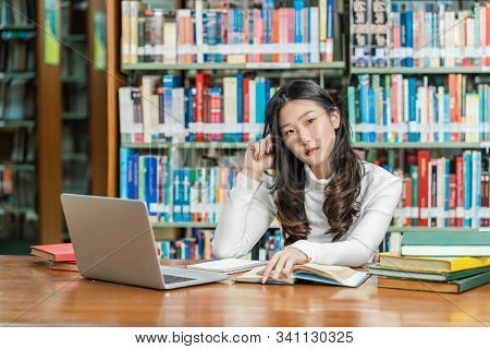 Asian Young Student In Casual Suit Thinking When Doing Homework And Using Technology Laptop In Libra