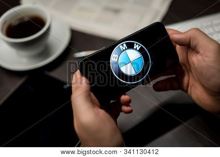 New York, New York / USA - 11 11 2019: Logo of BMW on the iPhone X in hands in office