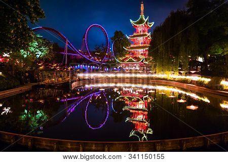 Night View Of The Amusement Park Tivoli Gardens In Copenhagen, Denmark