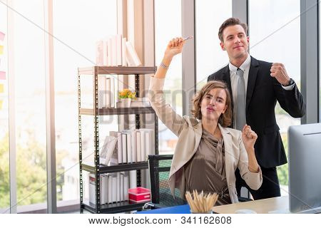 Mission Accomplished. Businesswoman And Businessman Are Happy And Raise Their Hands In Work Space Wi
