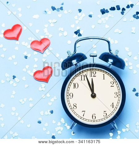 Alarm Clock On A Blue Background With Small Hearts. The Concept Of The Time Of Love, The Time Of Dat