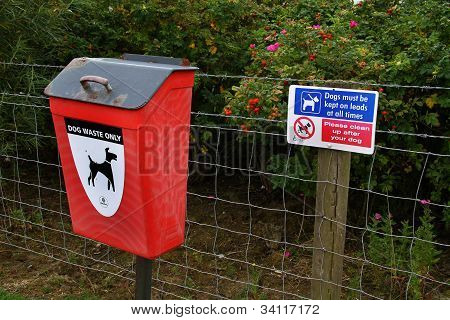 Dog fouling waste bin and warning notice on public footpath. poster