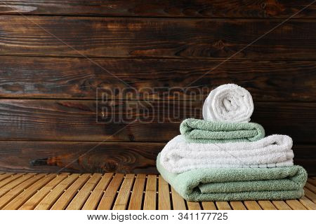 Folded Towels On Bamboo Table Against Wooden Background, Space For Text